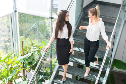#141145160 Two smiling business women talking while walking down stairs of modern office building. © Bojan Fotolia.de